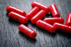 Red pills in capsules of anemia on a black table, selective focu